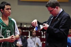 Árbitro fazendo o controle da raquete de Hugo Calderano